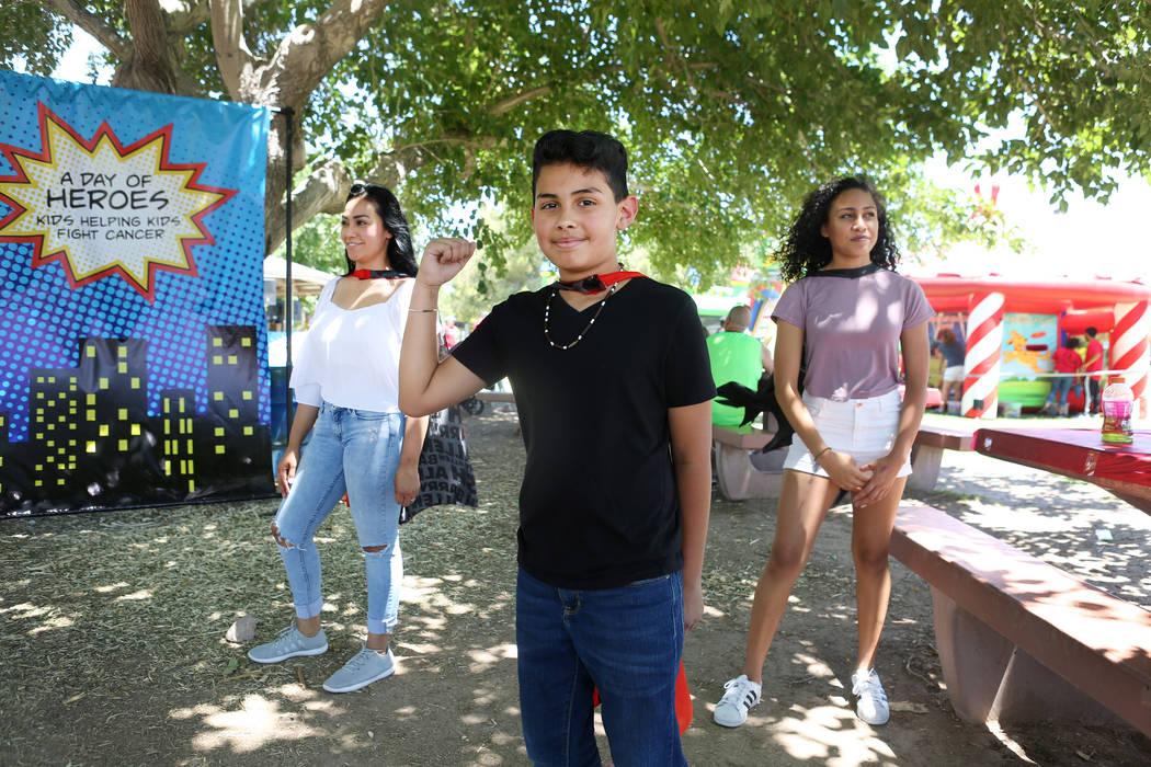 Francesco Mancia, 10, del centro, Nancy Marone, izquierda, y Victoria Marone, 14, usan capas durante la recaudación de fondos de Alex's Lemonade Stand Foundation para la investigación infantil q ...