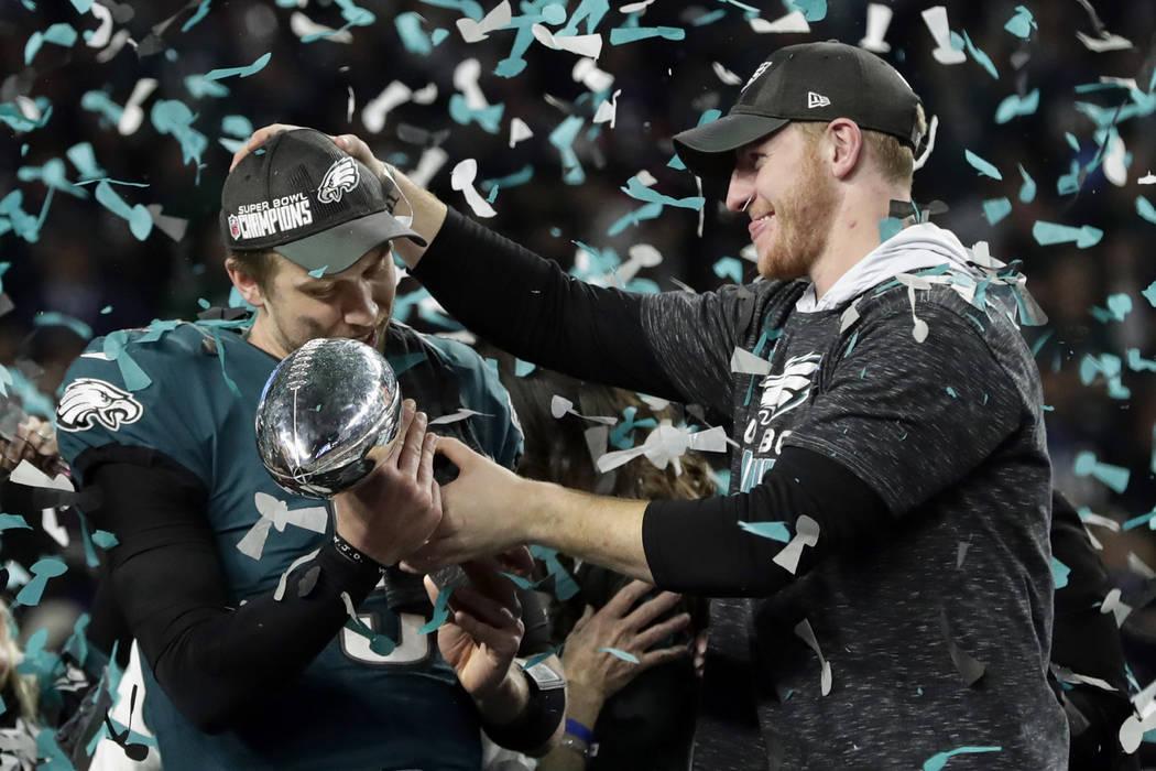 En esta foto del 4 de febrero de 2018, el mariscal de campo de los Eagles de Filadelfia, Carson Wentz, le entrega el trofeo Vincent Lombardi a Nick Foles después de ganar el juego de fútbol NFL ...