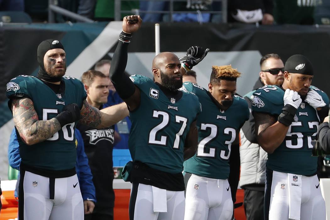 Chris Long, de los Philadelphia Eagles, desde la izquierda, Malcolm Jenkins y Rodney McLeod gesticulan durante el himno nacional antes de un partido de fútbol de la NFL contra los Chicago Bears, ...