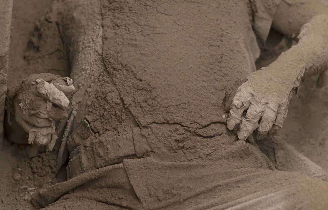 El cuerpo de una víctima está cubierto de cenizas volcánicas arrojadas por el Volcán de Fuego, en Escuintla, Guatemala, el lunes 4 de junio de 2018. Una ardiente erupción volcánica en el cen ...