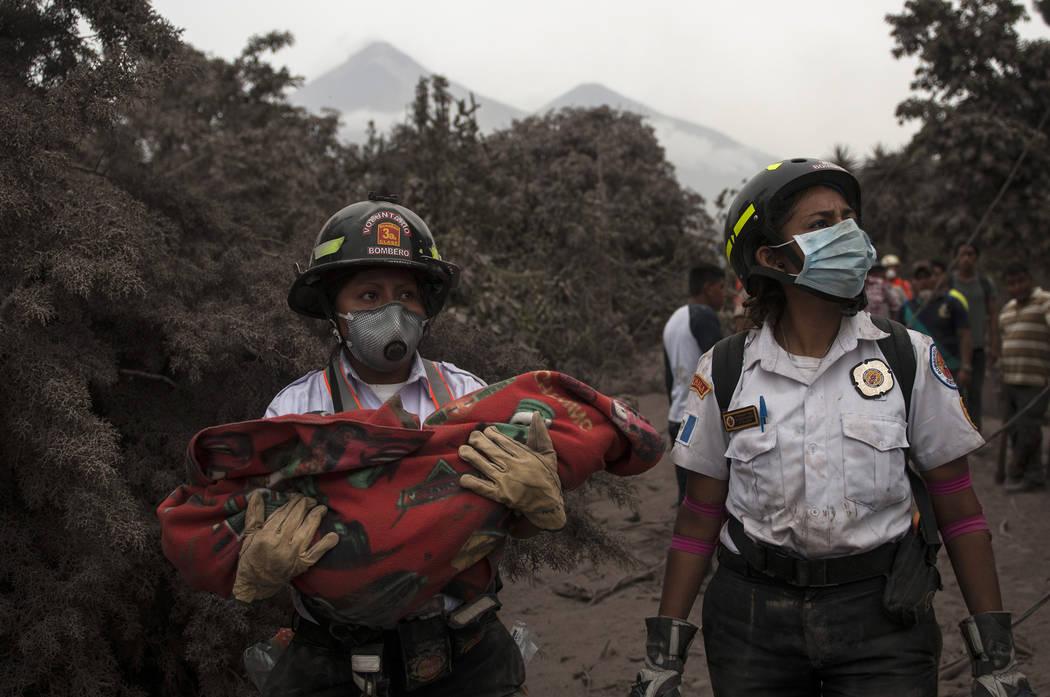 Un bombero lleva el cuerpo de un niño recuperado cerca del Volcán de Fuego, en Escuintla, Guatemala, el lunes 4 de junio de 2018. Una ardiente erupción volcánica en el centro-sur de Guatemala ...