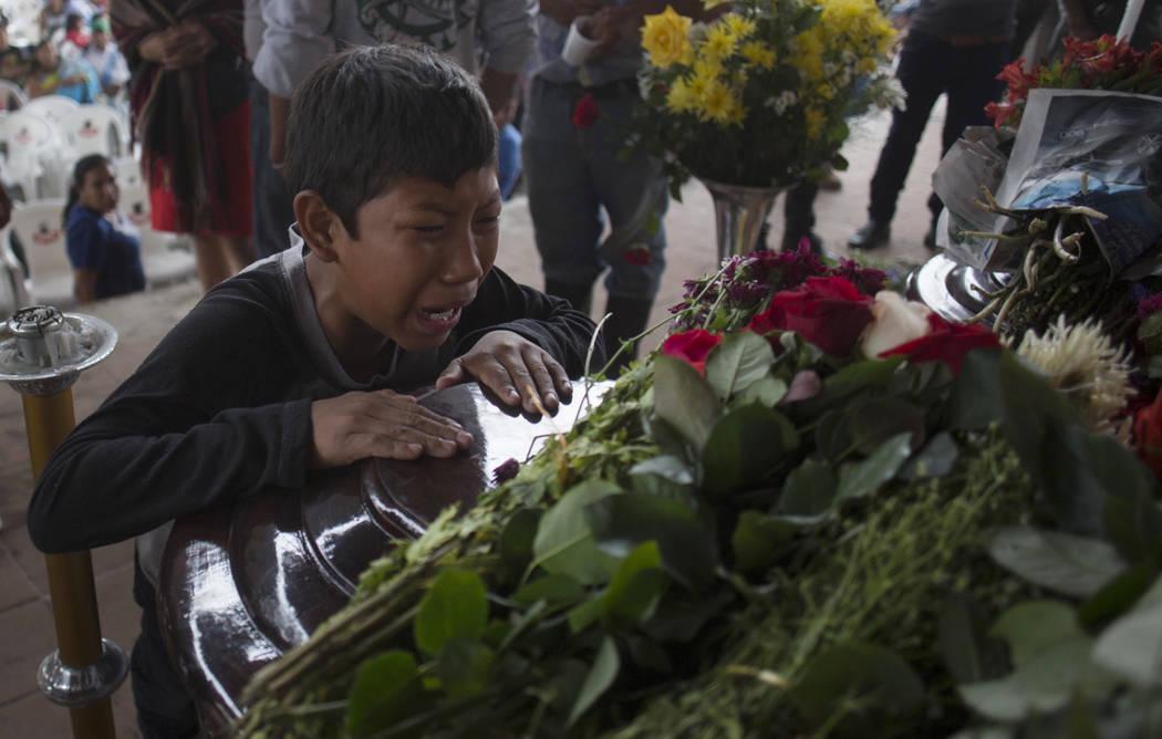Un joven llora sobre el ataúd de Nery Otoniel Gómez Rivas, de 17 años, cuyo cuerpo fue sacado de la ceniza volcánica durante la erupción del Volcán de Fuego, que en español significa Volcá ...