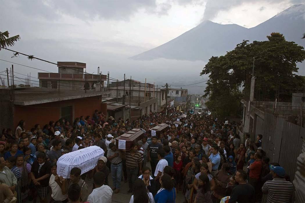 La gente carga los ataúdes de siete personas que murieron durante la erupción del Volcán de Fuego, al fondo, en el cementerio de San Juan Alotenango, Guatemala, el lunes 4 de junio de 2018. (Lu ...