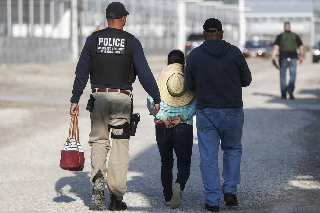 Agentes del gobierno retienen a una mujer sospechosa de vivir ilegalmente en el país durante una operación de inmigración en el Centro de Flores y Jardines de Corso en Castalia, Ohio, el martes ...