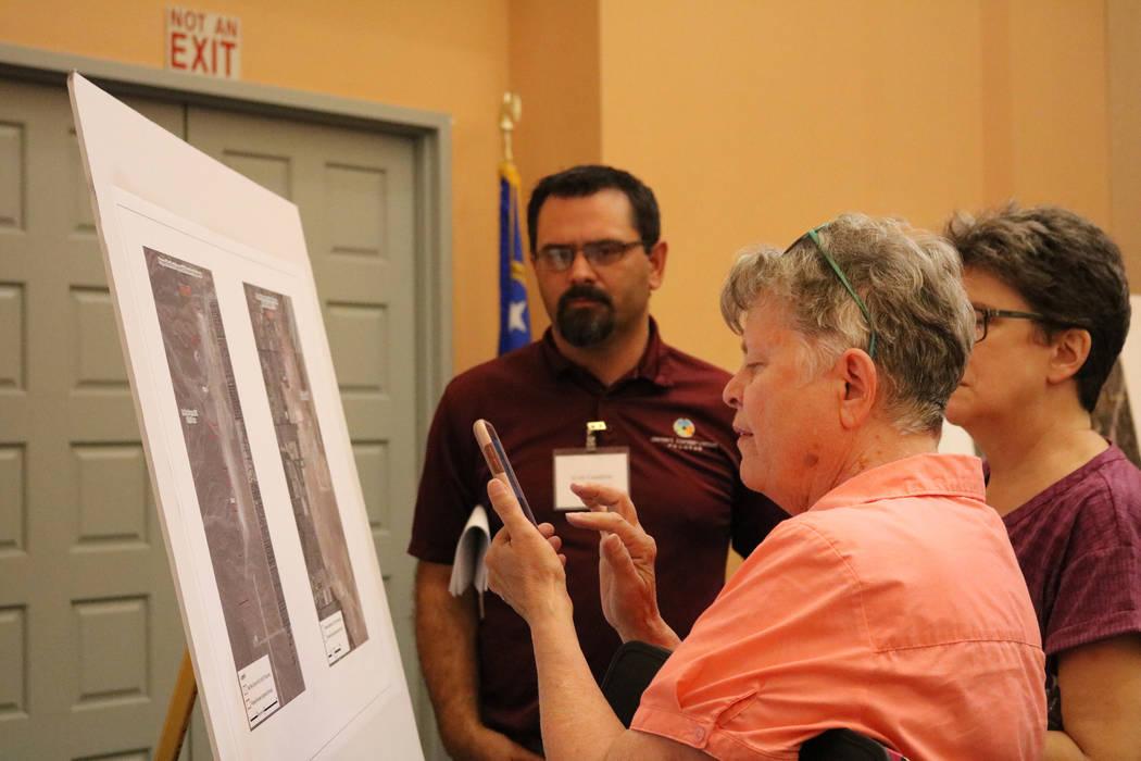 Jane Smith de Las Vegas revisa una cartulina mientras el biólogo Scott Cambrin del Condado de Clark explica un proyecto de ley de tierras públicas en la Biblioteca del Condado en Las Vegas, el m ...