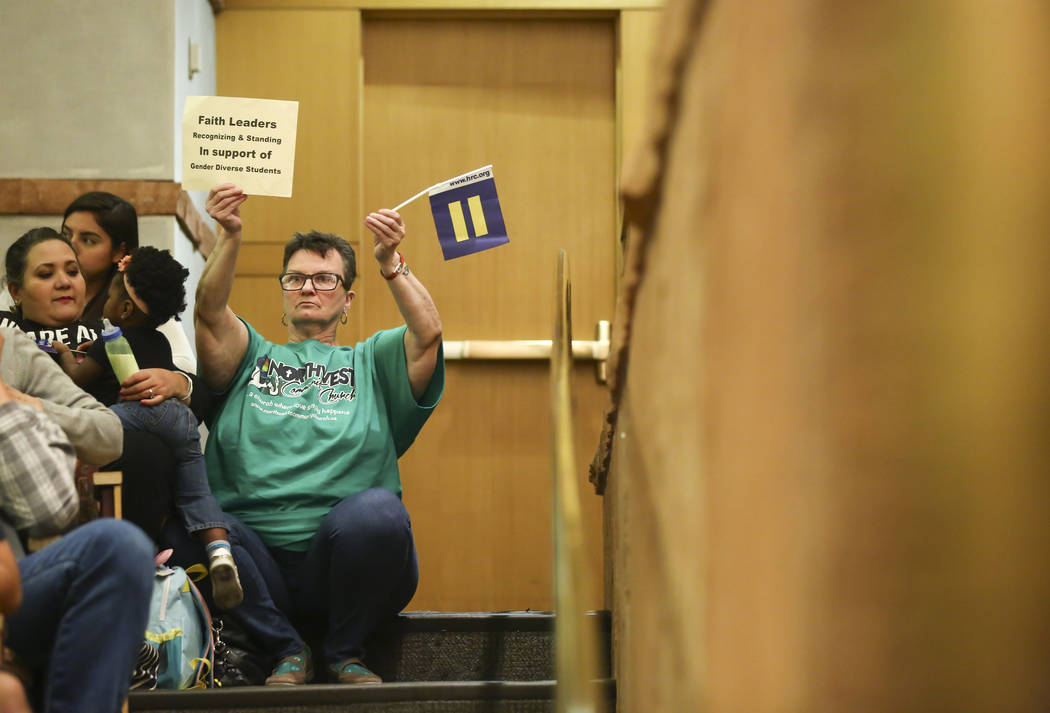Un asistente levanta un letrero que respalda una política de género para el distrito escolar durante una reunión de la Junta de Fideicomisarios del Distrito Escolar del Condado de Clark en el C ...