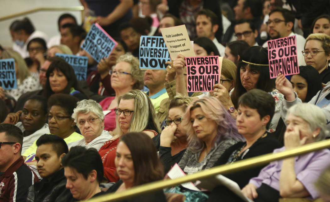 Los asistentes sostienen carteles en apoyo de una política de género diverso para el distrito escolar durante una reunión de la Junta de Fideicomisarios del Distrito Escolar del Condado de Clar ...