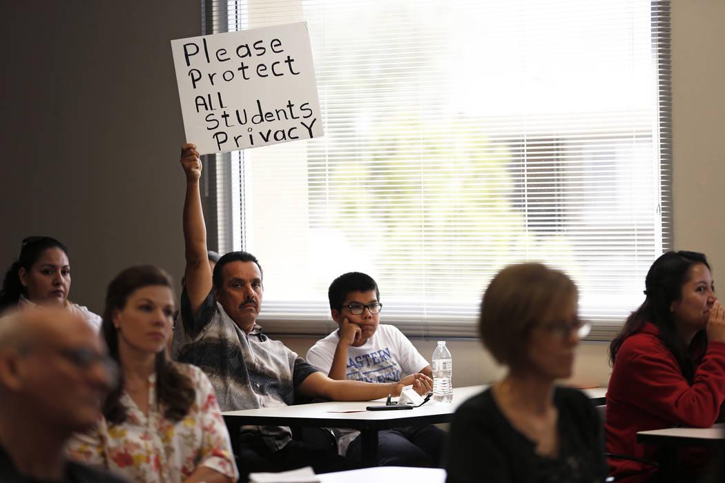 Gerardo González, del centro, y su hijo de 13 años, Joel, asisten a una audiencia sobre propuestas de normas de género en la sala de juntas del Departamento de Educación en Las Vegas el vierne ...