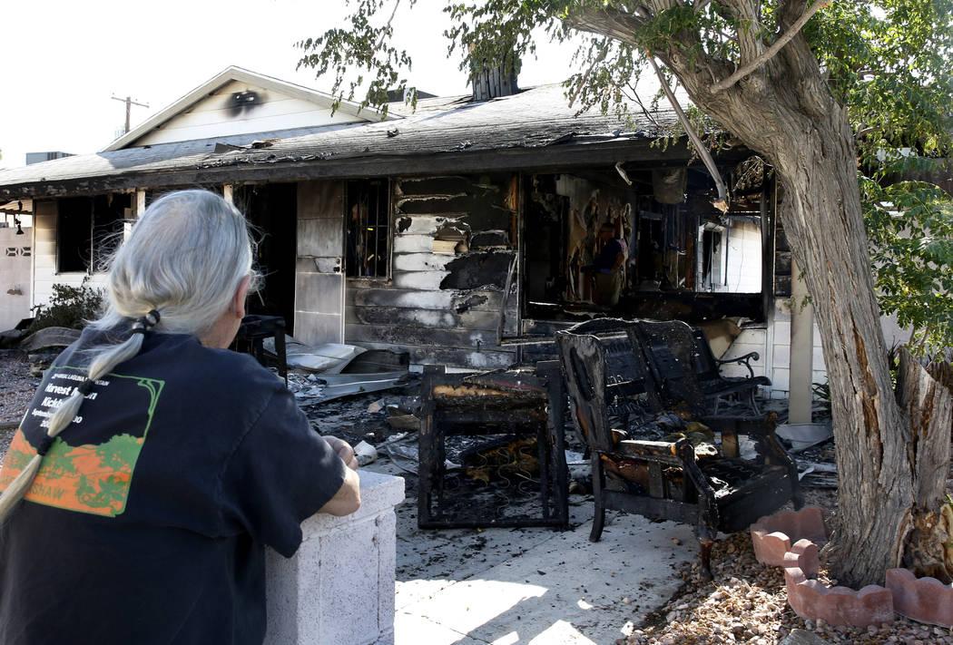 Un residente, que no quiso dar su nombre, observa mientras los bomberos del Condado de Clark investigan la causa del incendio de una casa en 5064 San Anselmo St., el jueves 7 de junio de 2018 en L ...