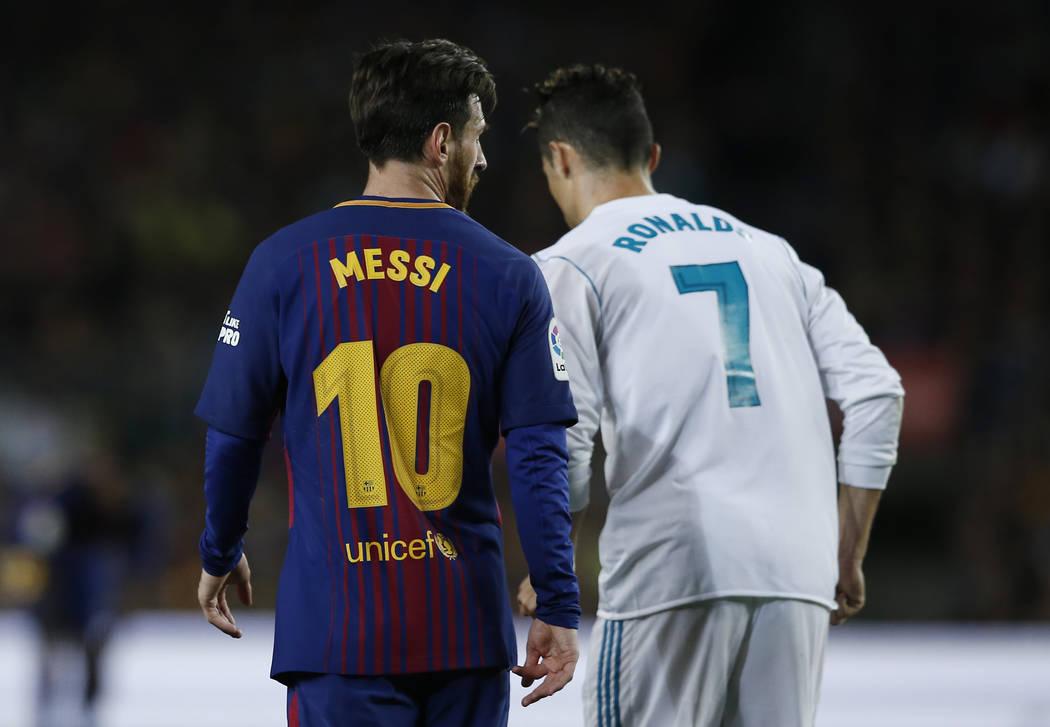 Lionel Messi, del Barcelona, y Cristiano Ronaldo, del Real Madrid, retroceden para tomar posiciones durante un partido de fútbol de la Liga española entre el Barcelona y el Real Madrid, denomina ...