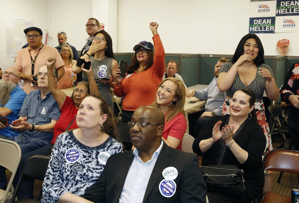 Partidarios, incluido Yan Gun, centro, de Henderson y Rose Mary Flores, segunda a la derecha, de Las Vegas reaccionan mientras ven los resultados de las elecciones de la elección primaria en una ...