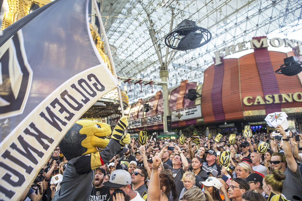 """Golden Knights mascot Chance, left, fires up the crowd during """"Stick Salute to Vegas and Our Fans"""" on Wednesday, June 13, 2018, at the Fremont Street Experience, in Las Vegas. Benjam ..."""