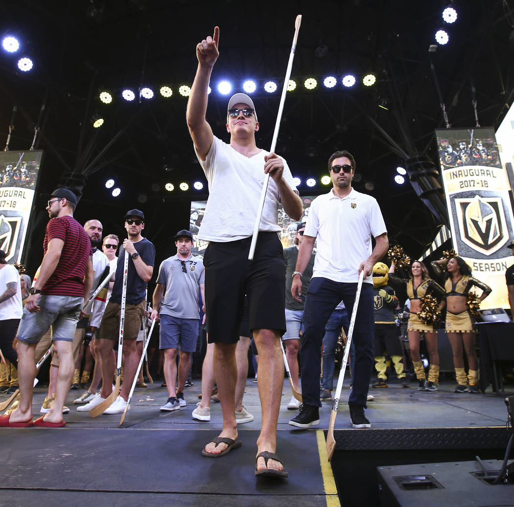 "Golden Knights defenseman Nate Schmidt, center, and right wing Alex Tuch, right, look to the crowd to hand out hockey sticks during the ""Stick Salute to Vegas and Our Fans"" held by the Golden Knig ..."