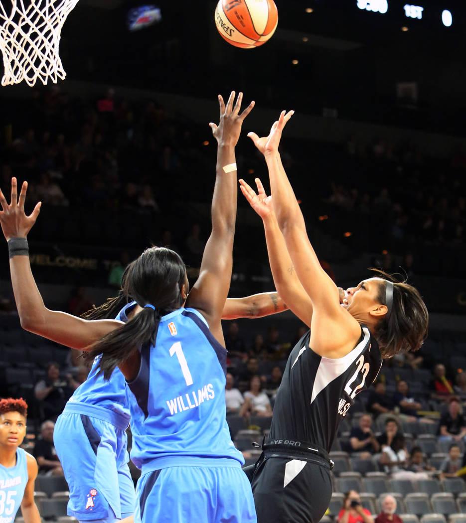 La centro de Las Vegas Aces, A'ja Wilson (22), busca un rebote contra Elizabeth Williams (1) de Atlanta Dreams en la primera mitad de un juego de baloncesto de la WNBA en el Mandalay Bay Event Cen ...