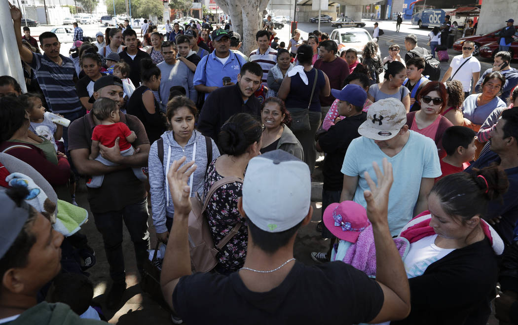 En esta foto del 13 de junio de 2018, un organizador, primer plano, habla a las familias mientras esperan para solicitar asilo político en los Estados Unidos, al otro lado de la frontera en Tijua ...