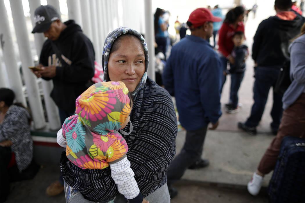 En esta foto del 13 de junio de 2018, María Rafaela Blancante, del estado mexicano de Michoacán, sostiene a su hija, Jazmin, mientras esperan con otras familias para pedir asilo político en los ...