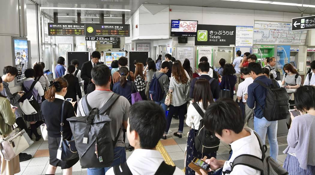 La gente espera la reanudación del servicio ferroviario que fue suspendido tras un terremoto, en la estación Nijo, Kyoto, oeste de Japón, el lunes 18 de junio de 2018. Un fuerte terremoto sacud ...