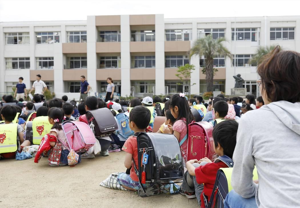 Los niños se refugian en el patio de la escuela en Ikeda, Osaka, después de un terremoto el lunes 18 de junio de 2018. Un fuerte terremoto sacudió la ciudad de Osaka en el oeste de Japón. Hay ...