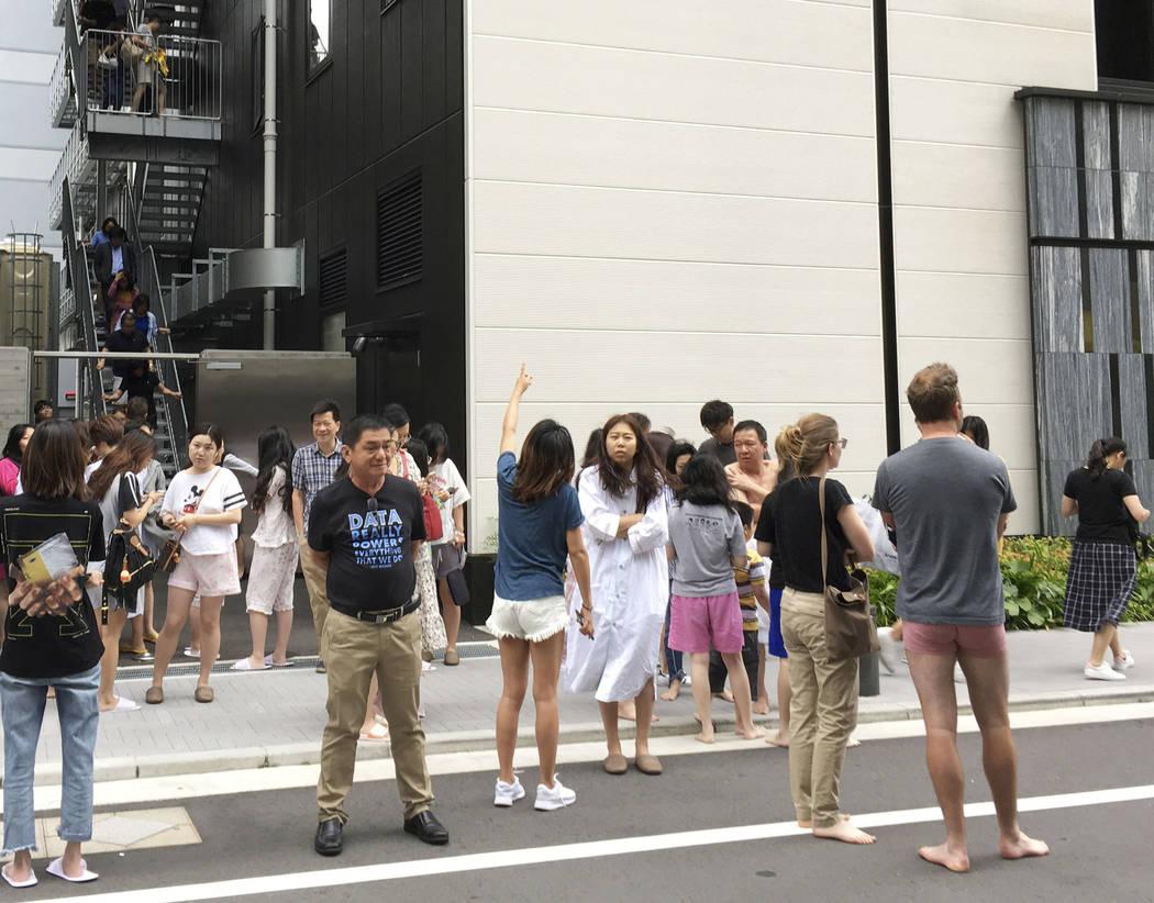 Los huéspedes se refugian frente a un hotel en Osaka tras un terremoto el lunes 18 de junio de 2018. Un fuerte terremoto sacudió la ciudad de Osaka en el oeste de Japón el lunes por la mañana, ...