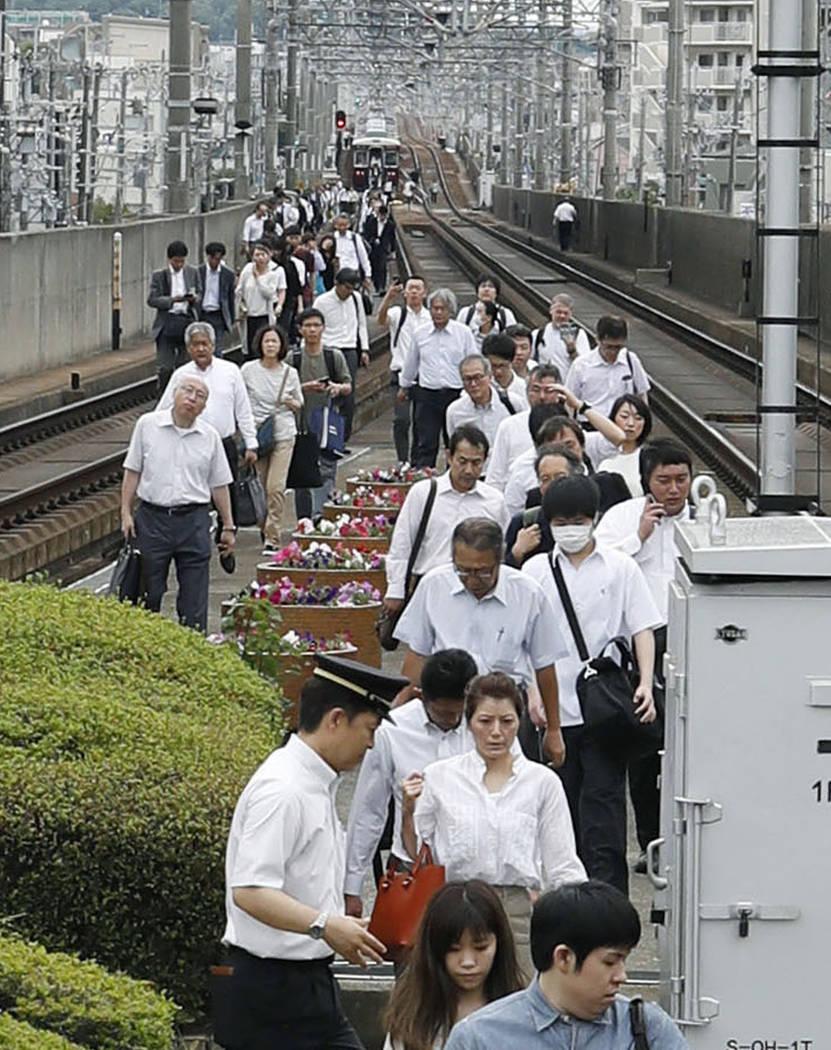 Los pasajeros caminan en las vías cuando el servicio del tren fue suspendido tras un terremoto en Takatsuki, Osaka, el lunes 18 de junio de 2018. Un fuerte terremoto sacudió la ciudad de Osaka e ...