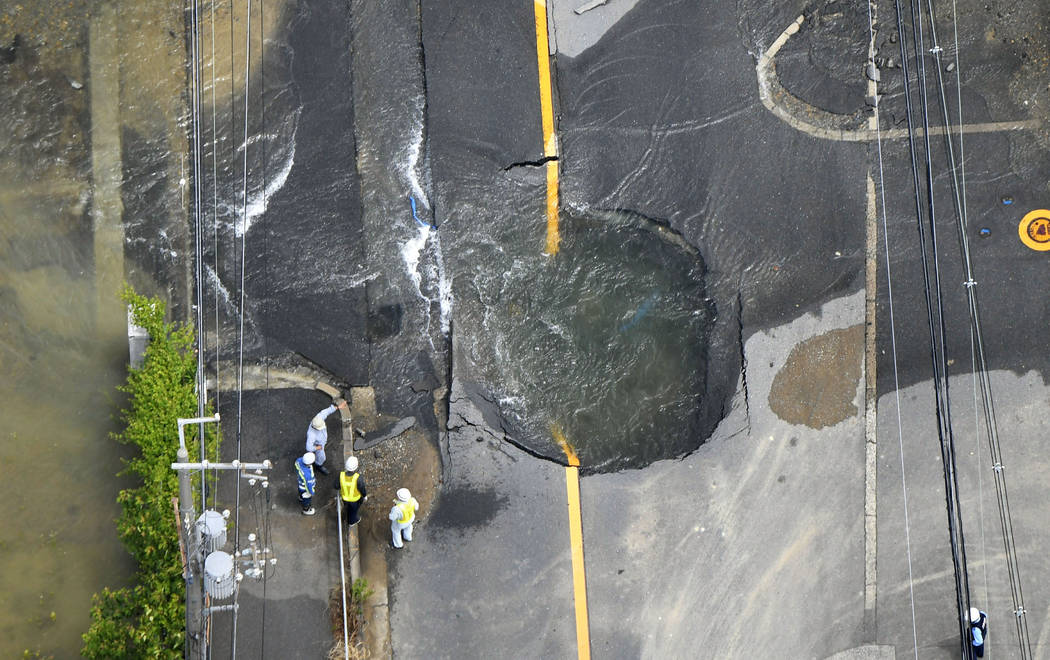 El agua se derrama de la grieta en la carretera, después de un terremoto en Takatsuki, Osaka, el lunes 18 de junio de 2018. Un fuerte terremoto derribó muros y provocó incendios dispersos en la ...
