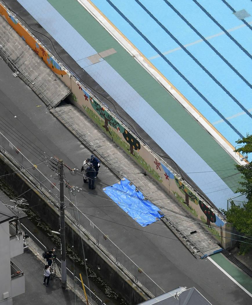 La policía inspecciona el sitio, cubierto por una sábana azul, donde una niña fue asesinada por una pared caída, después de un terremoto cerca de una escuela primaria en Takatsuki, Osaka, el ...