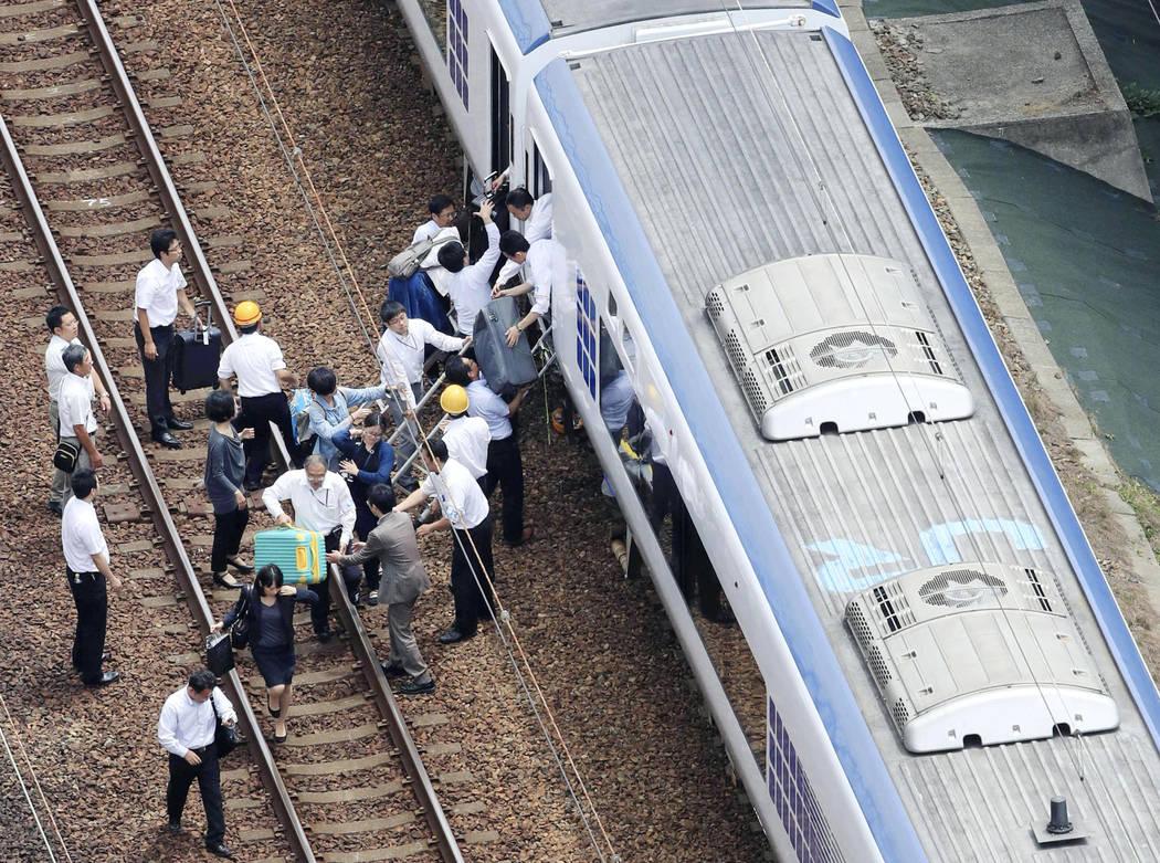 Los pasajeros descienden de un tren en la vía después de suspender el servicio ferroviario para verificar daños después de un terremoto en la ciudad de Takatsuki, Osaka, oeste de Japón, el lu ...