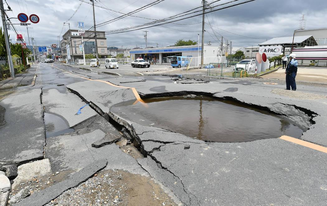 Una grieta se llena de agua en una carretera después de que se rompieron las tuberías de agua después de un terremoto en la ciudad de Takatsuki, Osaka, oeste de Japón, el lunes 18 de junio de ...