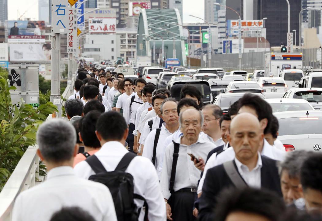 La gente camina sobre un puente mientras el tren y el servicio del metro fueron suspendidos para verificar daños después de un terremoto en Osaka, oeste de Japón, el lunes 18 de junio de 2018. ...