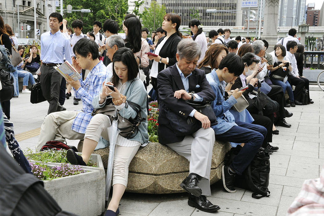 La gente espera que el servicio de trenes se reanude después de un terremoto en Osaka, el lunes 16 de junio de 2018. Un fuerte terremoto sacudió la ciudad de Osaka en el oeste de Japón el lunes ...