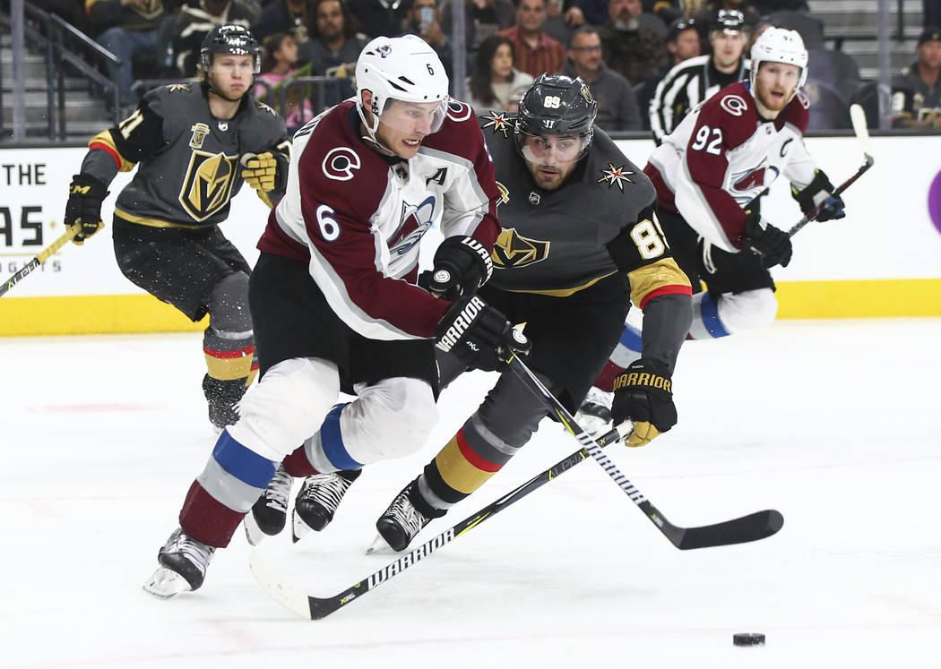 El alero derecho de los Golden Knights, Alex Tuch (89), trata de sacar el disco del defensor de los Colorado Avalanche, Erik Johnson (6), durante el tercer período de un juego de hockey NHL en T- ...