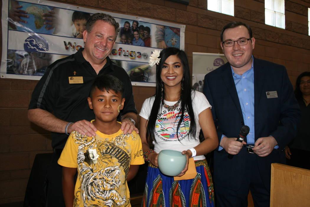 Thomas Roberts (izquierda atrás), una voluntaria y Milan Devetak, de Caridades Católicas. Al frente un niño de origen persa en el festival del Día del Refugiado, el 22 de junio del 2018. Foto ...