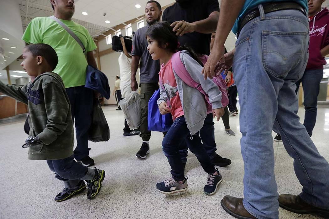Un grupo de inmigrantes de Honduras y Guatemala que buscan asilo llegan a la estación de autobuses después de que fueron procesados y puestos en libertad por la Aduana y Protección de Fronteras ...