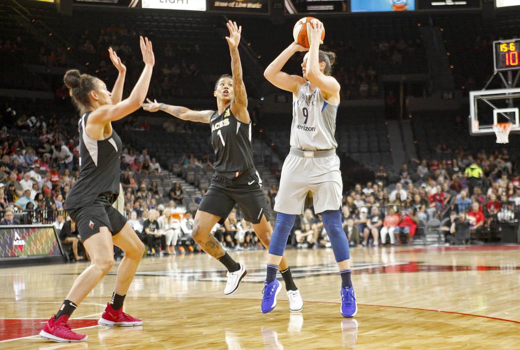 La delantera de Minnesota Lynx, Cecilia Zandalasini (9), tira para hacer una canasta contra la guardia de las Aces de Las Vegas, Kayla McBride (5) y la delantera Tamera Young (1) en un partido de ...