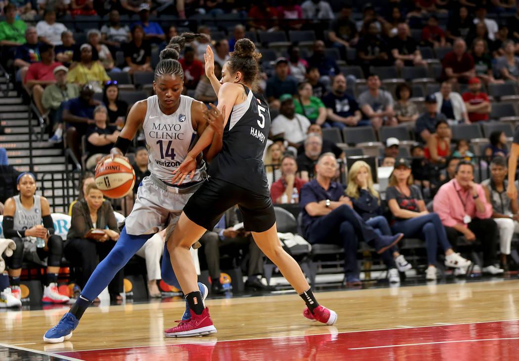 La centro de Minnesota Lynx, Temi Fagbenle (14), driblea alrededor de la alera de Las Vegas, Dearica Hamby (5), en la primera mitad de un partido de baloncesto de la WNBA en el Mandalay Bay Events ...