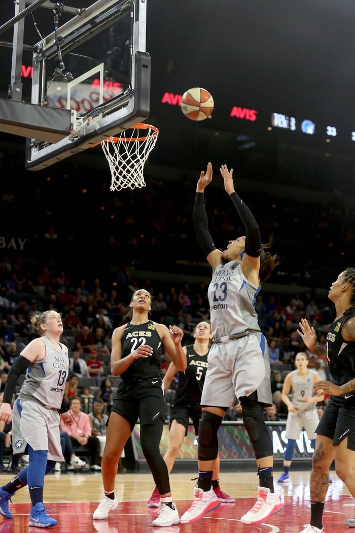 La alera de las Minnesota Lynx, Maya Moore (23), dispara para anotar contra la centro de Las Vegas Aces, A'ja Wilson (22), en la primera mitad de un juego de baloncesto de la WNBA en el Mandalay B ...