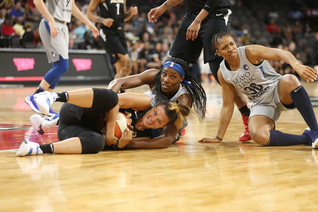 La guardia de las Aces de Las Vegas: Kayla McBride (21), agarra el balón de la centro Sylvia Fowles (34) y la guardia Tanisha Wright (30) en un partido de baloncesto de la WNBA en el Mandalay Bay ...
