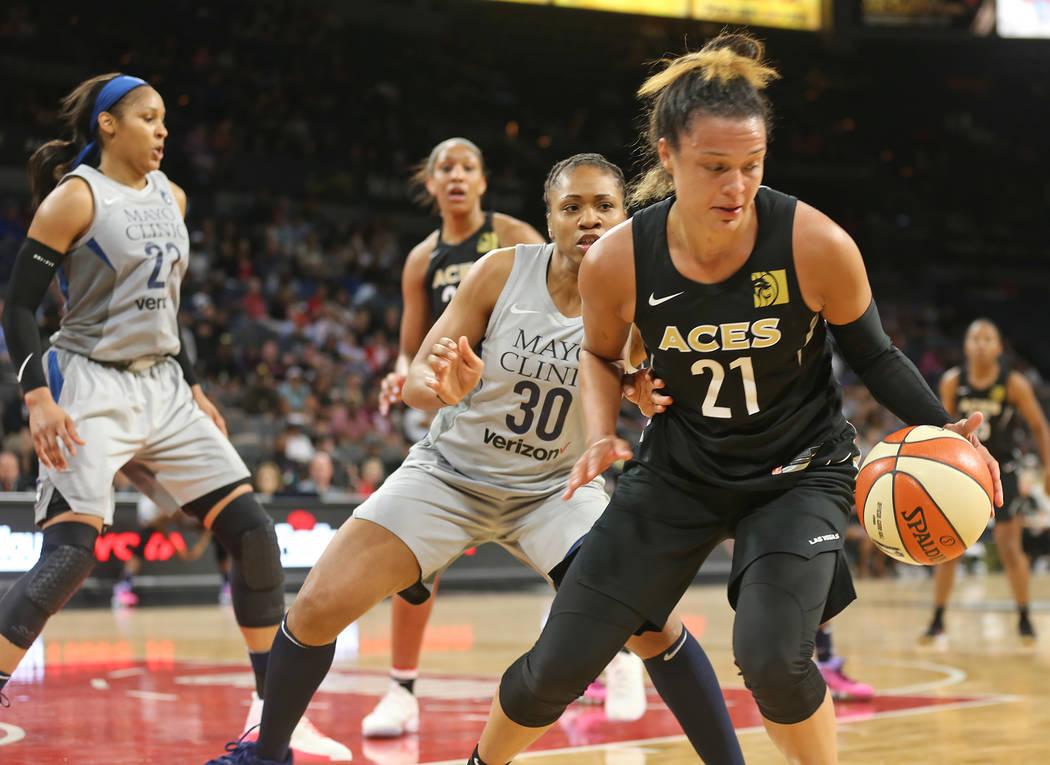 La guardia de las Aces de Las Vegas: Kayle McBride (21), custodia el balón de la guardia de las Minnesota Lynx: Tanisha Wright (30), en la segunda mitad de un partido de baloncesto de la WNBA en ...