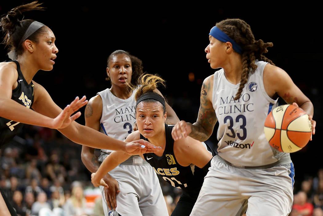 Seimone Augustus (33) de Minnesota Lynx intenta pasar el balón más allá de A'ja Wilson (22) de Las Vegas Aces y Kayla McBride (21) en la primer mitad de un juego de baloncesto WNBA en el Mandal ...