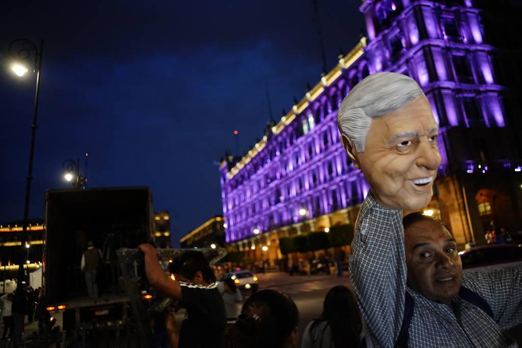 Un vendedor ambulante vende una máscara de Andrés Manuel López Obrador en la plaza principal de la Ciudad de México, el Zócalo, el domingo 1 de julio de 2018. López Obrador está a punto de ...