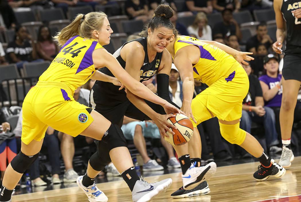 La jugadora de Aces, Kayla McBride (21), centro, intenta pasar la pelota a través de Karlos Samuelson (44) de Sparks durante la segunda mitad de un juego de baloncesto de la WNBA en el Mandalay B ...