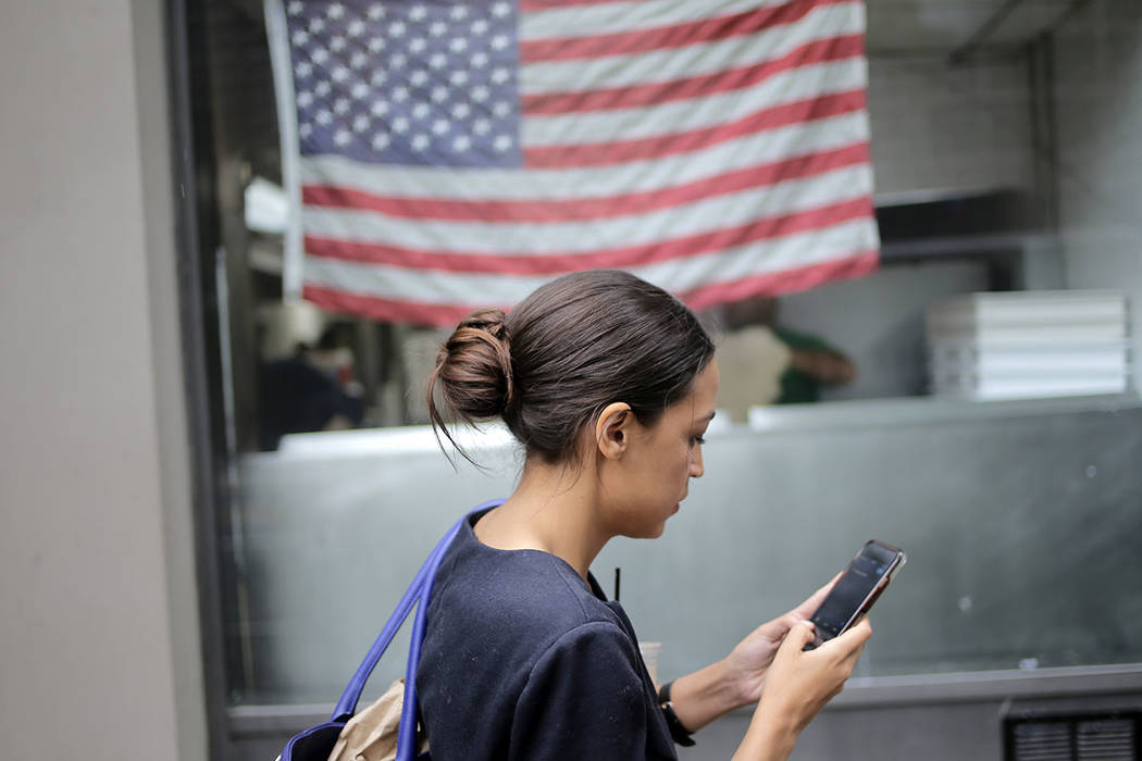 Alexandria Ocasio-Cortez revisa su teléfono mientras camina hacia su próxima cita en Nueva York, el miércoles 27 de junio de 2018. La recién llegada al poder político de 28 años que molestó ...