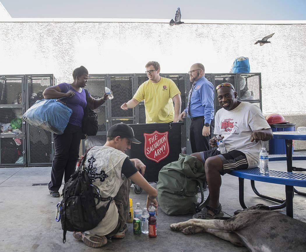 El monitor de refugios, Boston Brimhall, el coordinador de servicios para personas sin hogar y medio, Ryan McDonald, reparten agua en una estación de enfriamiento en The Salvation Army el jueves ...