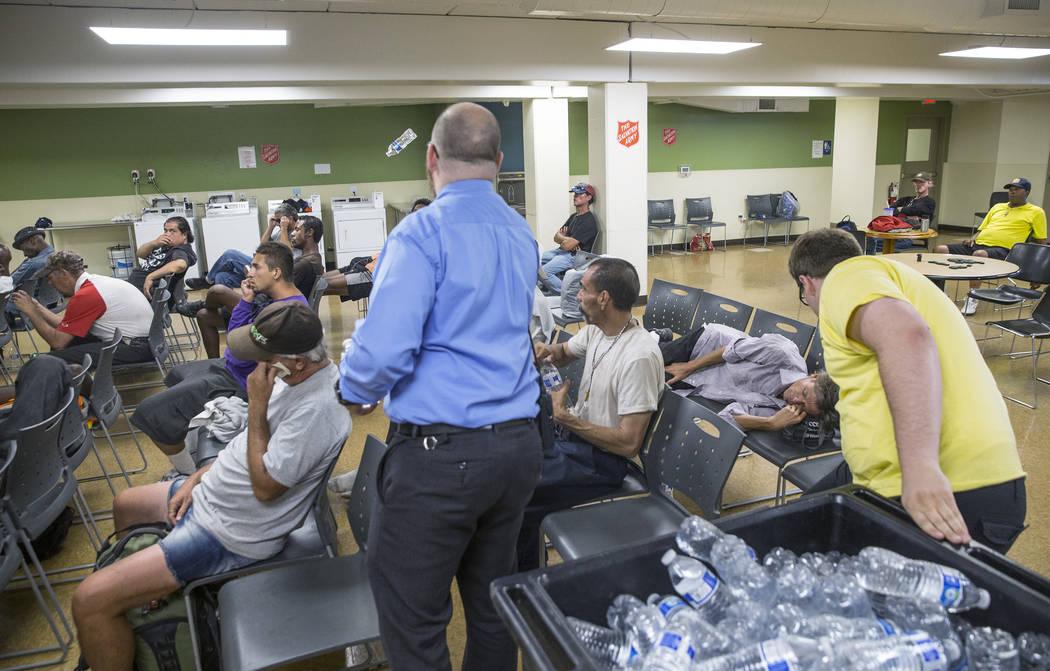 El monitor de refugios Boston Brimhall, a la derecha, y el coordinador de servicios para personas sin hogar, Ryan McDonald, repartirán agua en una estación de enfriamiento en The Salvation Army ...