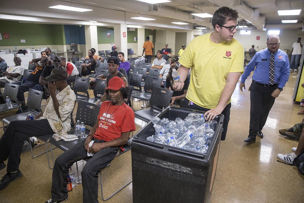 El monitor del albergue, Boston Brimhall, izquierda, y el coordinador de servicios para personas sin hogar, Ryan McDonald, reparten agua en una estación de enfriamiento en The Salvation Army el j ...