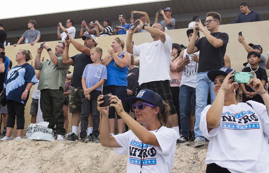 Los asistentes sacan sus teléfonos para capturar a Travis Pastrana saltando sobre 52 autos aplastados en una motocicleta Indian Scout FTR750 en el evento Evel Live donde Travis Pastrana intentó ...