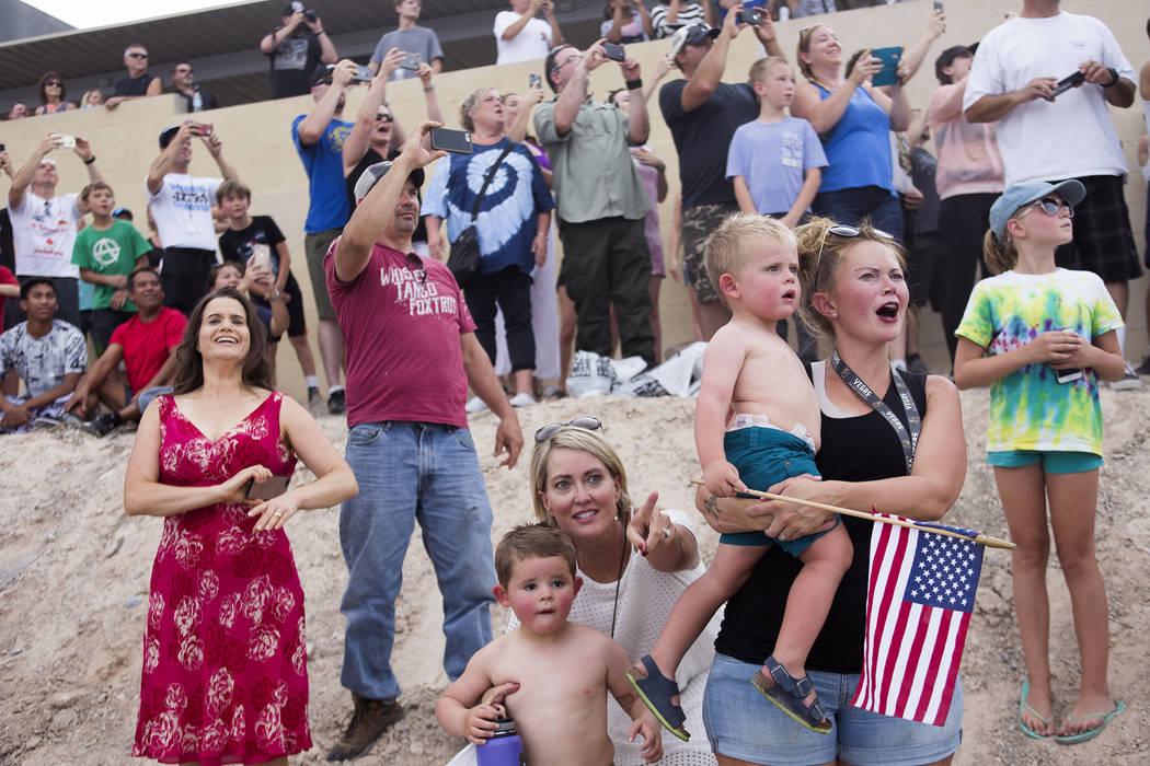 Julie Askim señala a su nieto Sawyer Tuck, de 4 años, mientras Jessica Tuck sostiene a su hijo Oliver Tuck, de 2, mientras ven a Travis Pastrana saltar 52 autos aplastados en una motocicleta Ind ...