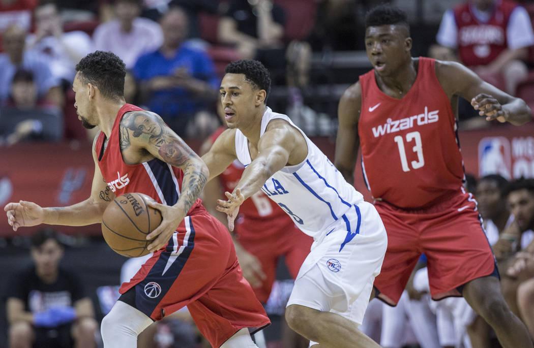 El guardia de los Philadelphia 76ers, Zhaire Smith (8), defiende al guardia de los Washington Wizards, Chris Chiozza (33), durante la Liga de verano de la NBA el lunes 9 de julio de 2018 en el Tho ...