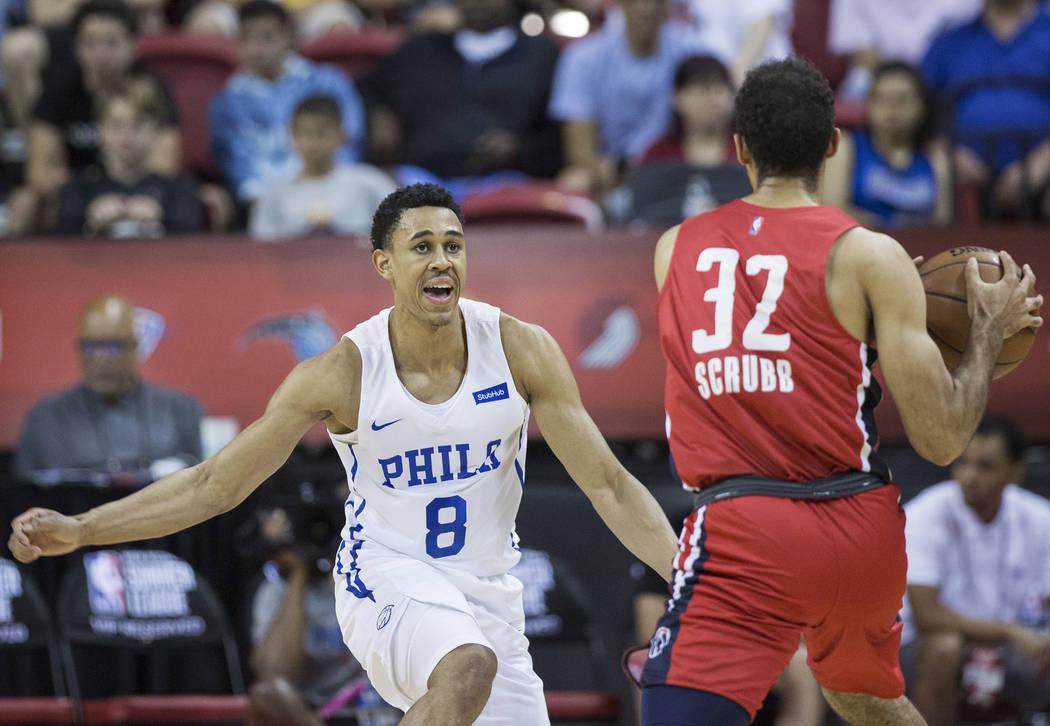 El guardia de los Philadelphia 76ers, Zhaire Smith (8), defiende al escolta de los Washington Wizards, Philip Scrubb (32), durante la Liga de verano de la NBA el lunes 9 de julio de 2018 en el Tho ...