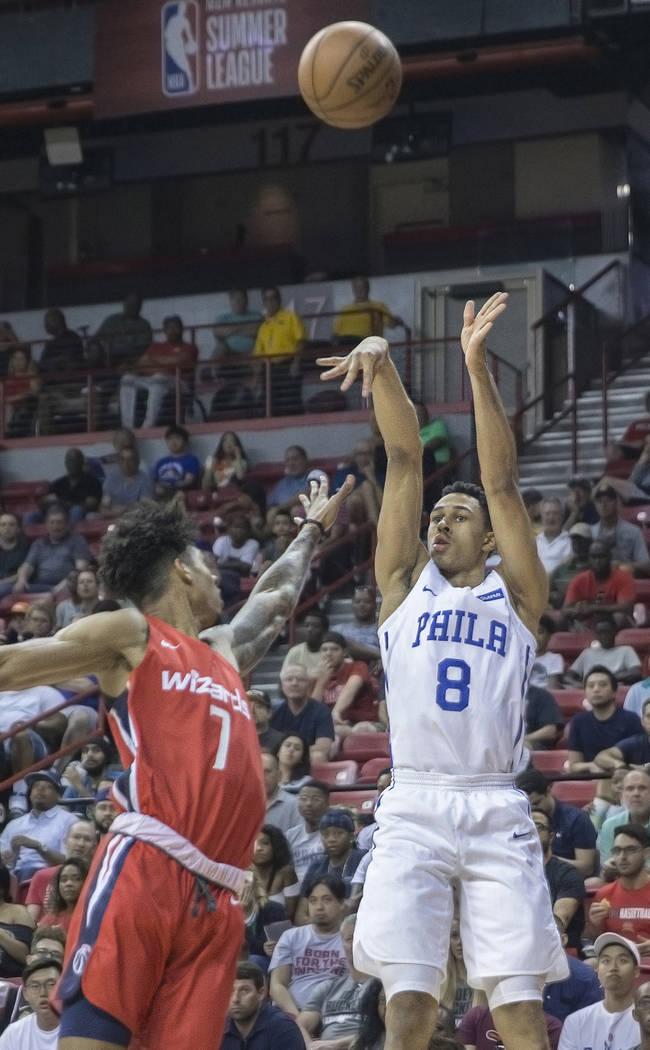 El guardia de Philadelphia 76ers, Zhaire Smith (8), lanza un tiro de esquina sobre el alero de los Wizards de Washington, Devin Robinson (7), durante la Liga de verano de la NBA el lunes 9 de juli ...